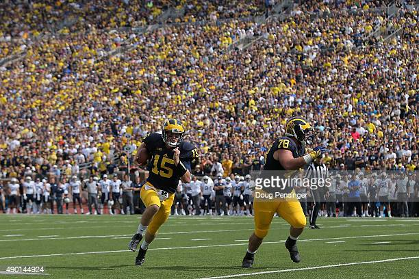 Quarterback Jake Rudock of the Michigan Wolverines follows teammate Erik Magnuson of the Michigan Wolverines as he carries the ball four yards for a...