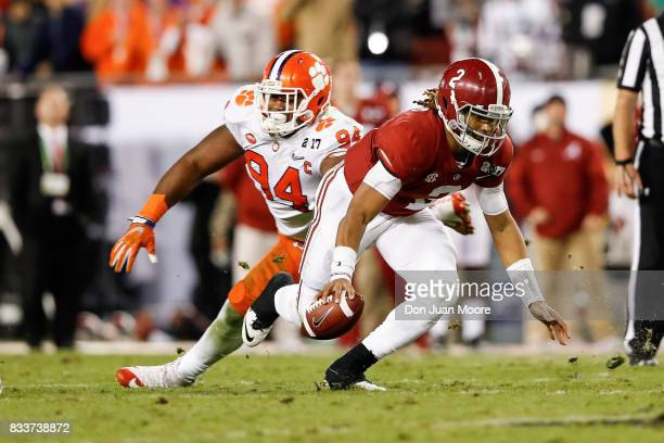 Quarterback Jalen Hurts of the Alabama Crimson Tide avoids a tackle from Defensive Tackle Carlos Watkins during the 2017 College Football Playoff...