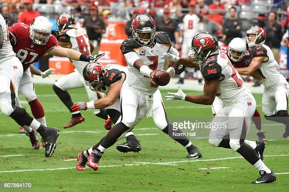 Quarterback Jameis Winston hands the ball off to running back Doug Martin of the Tampa Bay Buccaneers during the first quarter of the NFL game...