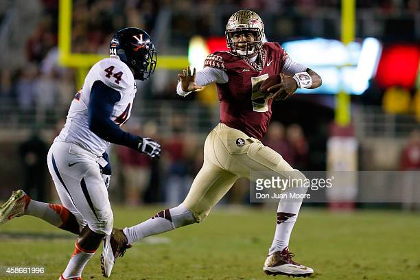 Quarterback Jameis Winston of the Florida State Seminoles give a stiff arm to Linebacker Henry Coley the Virginia Cavaliers during the game at Doak...