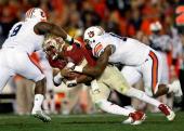 Quarterback Jameis Winston of the Florida State Seminoles is sacked by linebacker Cassanova McKinzy and defensive end LaDarius Owens of the Auburn...