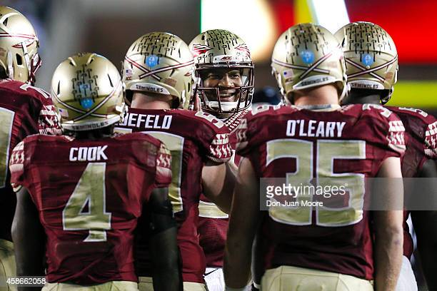 Quarterback Jameis Winston of the Florida State Seminoles talks with his teammates in the huddle during the game against the Virginia Cavaliers at...