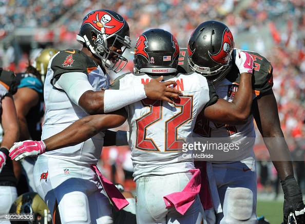 Quarterback Jameis Winston of the Tampa Bay Buccaneers celebrates along with tackle Kevin Pamphile of the Tampa Bay Buccaneers after running back...