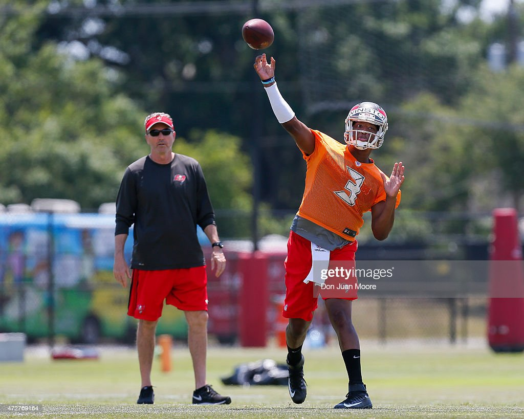 Quarterback Jameis Winston #3 of the Tampa Bay Buccaneers on a pass play during Rookie Mini Camp as Offensive Coordinator Dirk Koetter looks on at One Buccaneer Place on May 9, 2015 in Tampa, Florida.