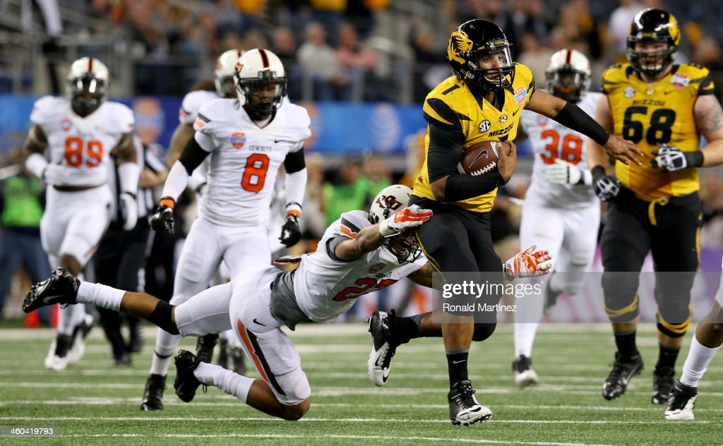 Quarterback James Franklin #1 of the Missouri Tigers runs the ball for 16-yards against Lyndell Johnson #27 of the Oklahoma State Cowboys in the second quarter during the AT&T Cotton Bowl on January 3, 2014 in Arlington, Texas.