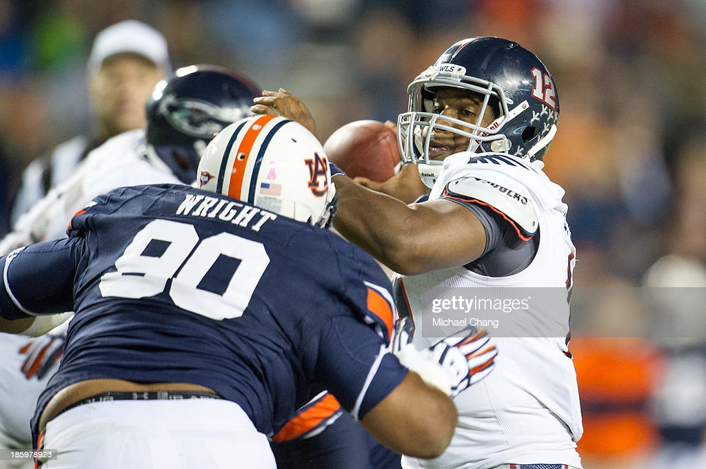 Quarterback Jaquez Johnson #12 of the Florida Atlantic Owls prepares to throw a pass before being hit by defensive lineman Gabe Wright #90 of the Auburn Tigers on October 26, 2013 at Jordan-Hare Stadium in Auburn, Alabama. Auburn defeated Florida Atlantic 45-10.