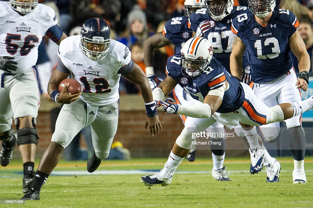 Quarterback Jaquez Johnson #12 of the Florida Atlantic Owls runs past linebacker Kris Frost #17 of the Auburn Tigers during the first quarter of play on October 26, 2013 at Jordan-Hare Stadium in Auburn, Alabama. At the end of the first quarter Auburn leads Florida Atlantic 21-0.