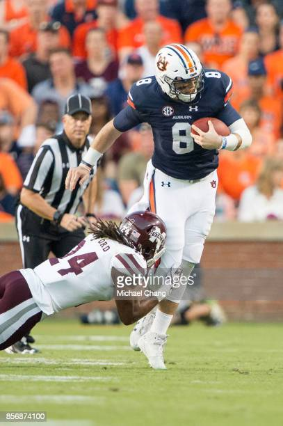 Quarterback Jarrett Stidham of the Auburn Tigers looks to escape a tackle by defensive back Chris Rayford of the Mississippi State Bulldogs at...