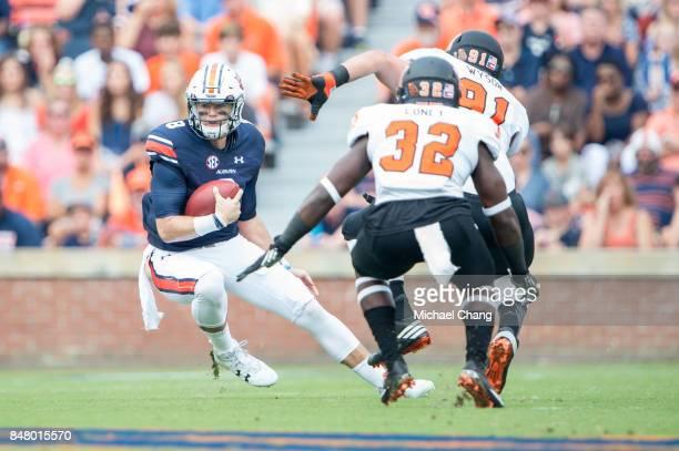 Quarterback Jarrett Stidham of the Auburn Tigers looks to maneuver by defensive lineman Austin Wysor of the Mercer Bears and defensive back Brandon...
