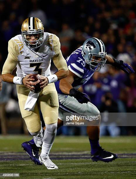 Quarterback Jarrett Stidham of the Baylor Bears scrambles as defensive end Jordan Willis of the Kansas State Wildcats chases during the 1st quarter...
