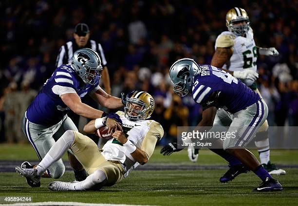 Quarterback Jarrett Stidham of the Baylor Bears slides as defensive tackle Travis Britz and defensive end Marquel Bryant of the Kansas State Wildcats...