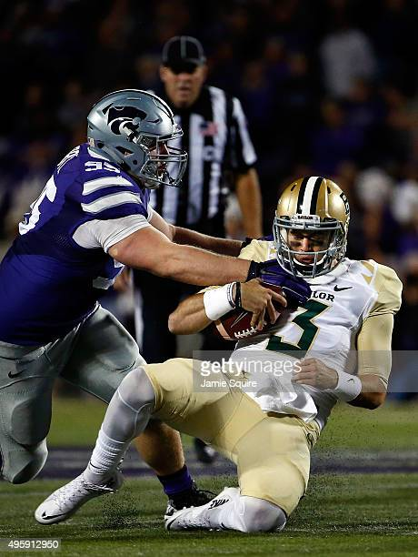 Quarterback Jarrett Stidham of the Baylor Bears slides as defensive tackle Travis Britz of the Kansas State Wildcats defends during the 1st quarter...
