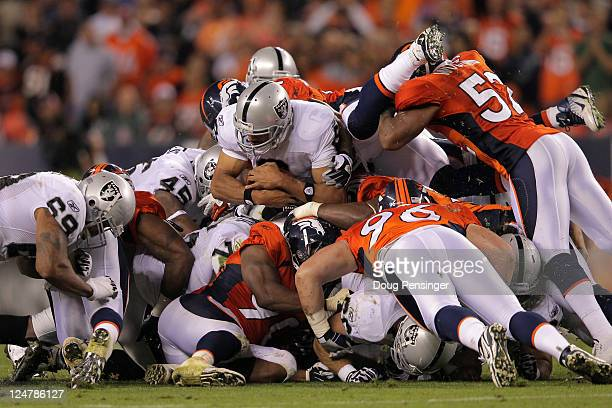 Quarterback Jason Campbell of the Oakland Raiders is tackled after an attempted quarterback sneak in the first half against the Denver Broncos at...