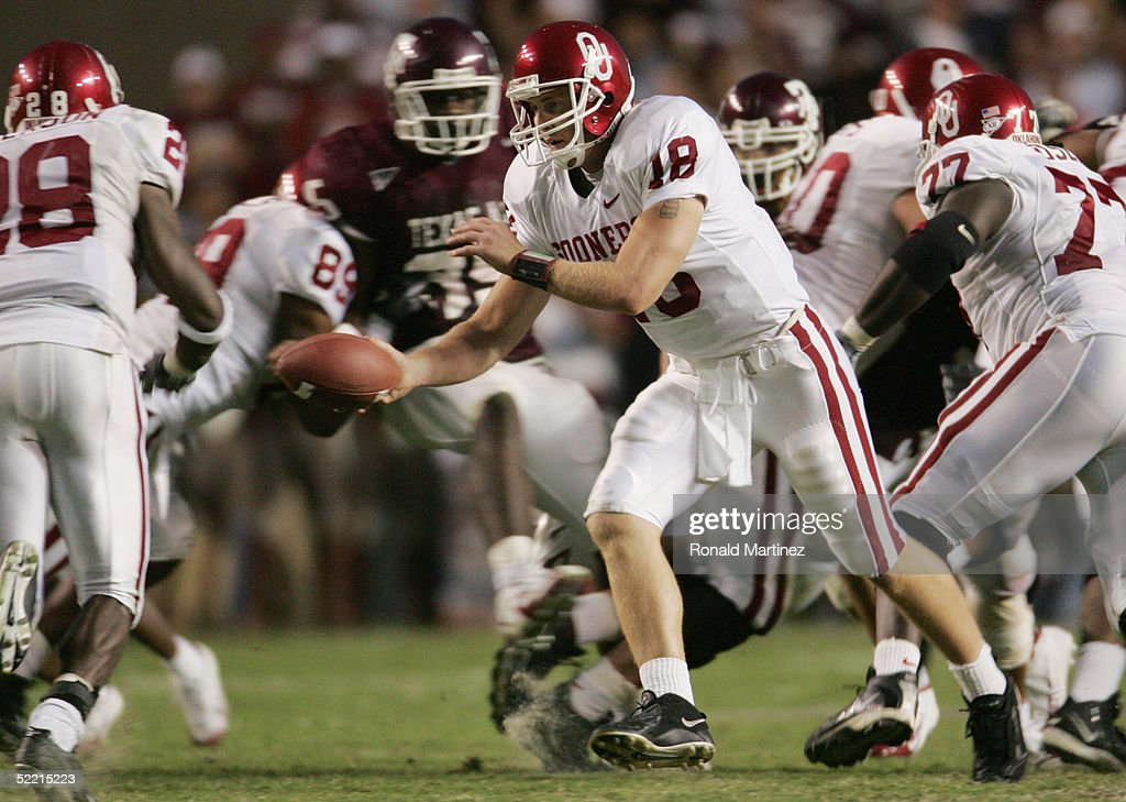 Quarterback Jason White #18 of the University of Oklahoma Sooners hands-off the ball against the Texas A&M University Aggies on November 6, 2004 at Kyle Field in College Station, Texas. The Sooners defeated the Aggies 42-35.