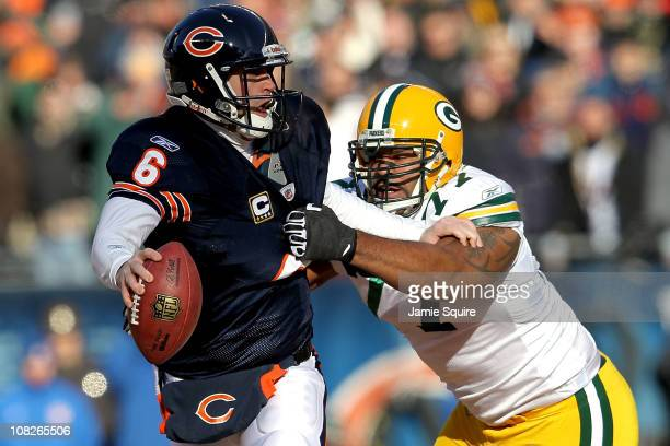 Quarterback Jay Cutler of the Chicago Bears attempts to avoid a sack by Cullen Jenkins of the Green Bay Packers in the first quarter of the NFC...