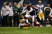 Quarterback Jay Cutler of the Chicago Bears jumps over the reach of Frank Zombo of the Green Bay Packers at Soldier Field on September 27 2010 in...