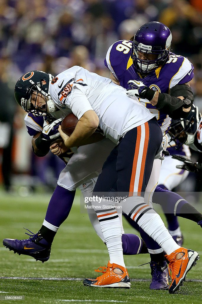 Quarterback Jay Cutler#6 of the Chicago Bears is tackled by Jamarca Sanford #33 and Brian Robison #96 of the Minnesota Vikings at Mall of America Field on December 9, 2012 in Minneapolis, Minnesota.