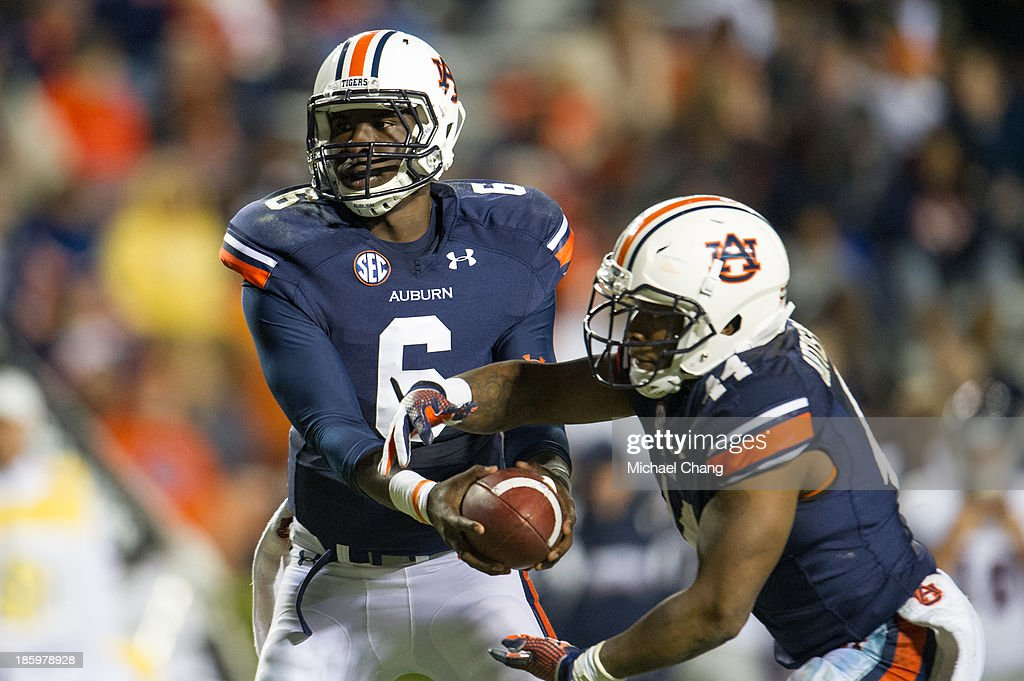 Quarterback Jeremy Johnson #6 of the Auburn Tigers hands the ball off to quarterback Nick Marshall #14 of the Auburn Tigers during their game against the Florida Atlantic Owls on October 26, 2013 at Jordan-Hare Stadium in Auburn, Alabama. Auburn defeated Florida Atlantic 45-10.