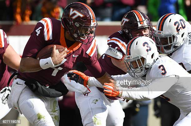 Quarterback Jerod Evans of the Virginia Tech Hokies carries the ball as safety Quin Blanding of the Virginia Cavaliers attempts the tackle in the...
