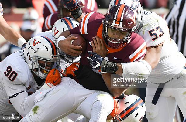 Quarterback Jerod Evans of the Virginia Tech Hokies is tackled by inside linebacker Micah Kiser and defensive end Jack Powers of the Virginia...