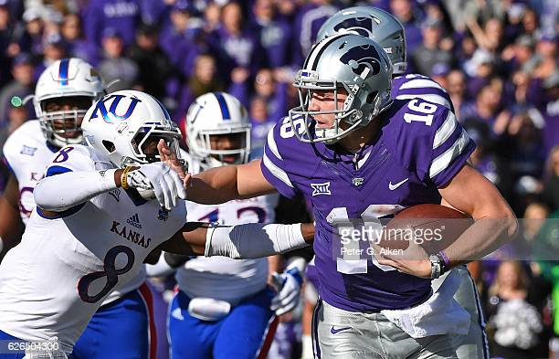 Quarterback Jesse Ertz of the Kansas State Wildcats puts out a stiffarm against defensive back Brandon Stewart of the Kansas Jayhawks during the...