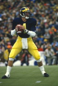 Quarterback Jim Harbaugh of the Michigan Wolverines drops back to pass during an NCAA football game circa 1986 at Michigan Stadium in Ann Arbor...