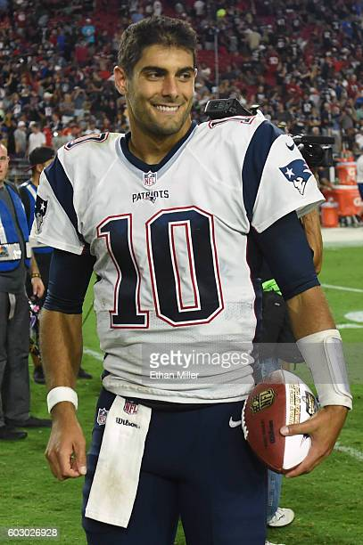 Quarterback Jimmy Garoppolo of the New England Patriots smiles as he walks off the field after the NFL game against the Arizona Cardinals at...