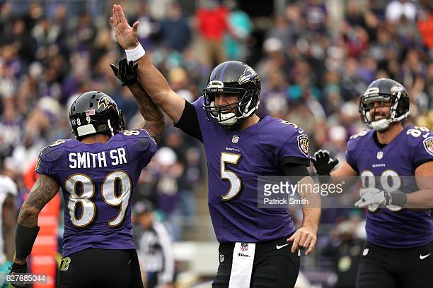 Quarterback Joe Flacco of the Baltimore Ravens celebrates with teammate wide receiver Steve Smith after tight end Dennis Pitta scored a second...