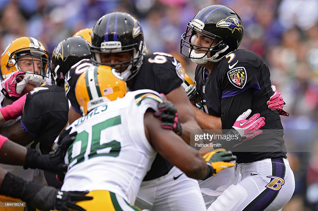Quarterback <a gi-track='captionPersonalityLinkClicked' href=/galleries/search?phrase=Joe+Flacco&family=editorial&specificpeople=4645672 ng-click='$event.stopPropagation()'>Joe Flacco</a> #5 of the Baltimore Ravens is sacked in the third quarter against the Green Bay Packers at M&T Bank Stadium on October 13, 2013 in Baltimore, Maryland.