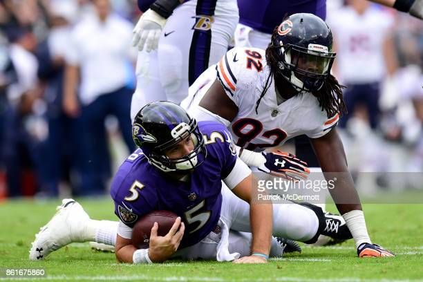 Quarterback Joe Flacco of the Baltimore Ravens is tackled by outside linebacker Pernell McPhee of the Chicago Bears in the second quarter at MT Bank...