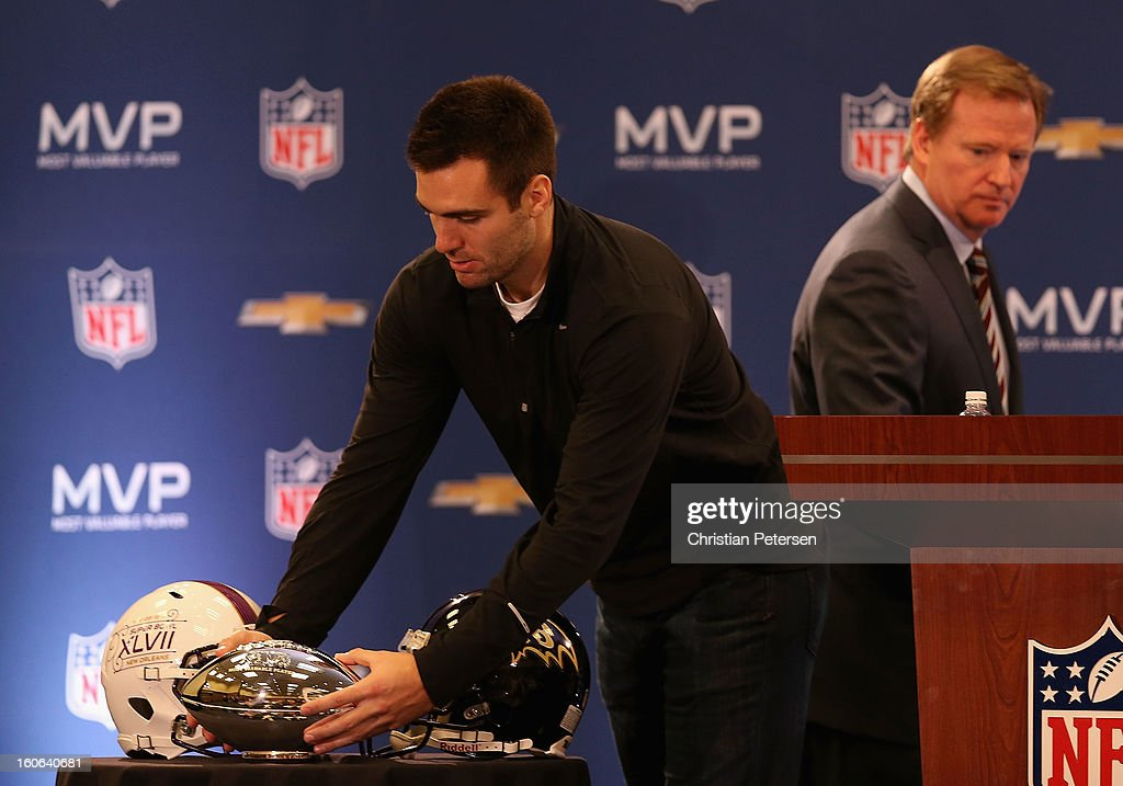 Quarterback Joe Flacco of the Baltimore Ravens picks up the MVP trophy after being introduced by NFL Commissioner Roger Goodell (R) during the Super Bowl XLVII Team Winning Coach and MVP Press Conference at the Ernest N. Morial Convention Center on February 4, 2013 in New Orleans, Louisiana.