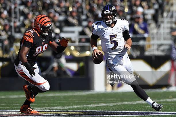 Quarterback Joe Flacco of the Baltimore Ravens rushes past defensive end Carlos Dunlap of the Cincinnati Bengals in the fourth quarter MT Bank...