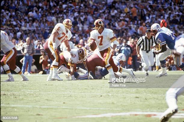 Quarterback Joe Theismann of the Washington Redskins scrambles against the Houston Oilers at RFK Stadium on September 15 1985 in Washington DC The...