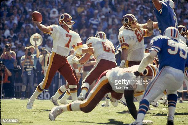 Quarterback Joe Theismann of the Washington Redskins sets up to pass behind the block of guard Ken Huff against the Houston Oilers at RFK Stadium on...