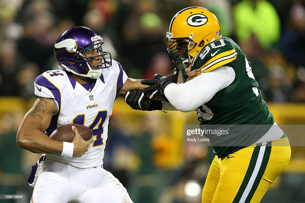 Quarterback <a gi-track='captionPersonalityLinkClicked' href=/galleries/search?phrase=Joe+Webb&family=editorial&specificpeople=5222364 ng-click='$event.stopPropagation()'>Joe Webb</a> #14 of the Minnesota Vikings tries to push back nose tackle <a gi-track='captionPersonalityLinkClicked' href=/galleries/search?phrase=B.J.+Raji&family=editorial&specificpeople=2167649 ng-click='$event.stopPropagation()'>B.J. Raji</a> #90 of the Green Bay Packers to avoid a sack in the second quarter during the NFC Wild Card Playoff game at Lambeau Field on January 5, 2013 in Green Bay, Wisconsin.