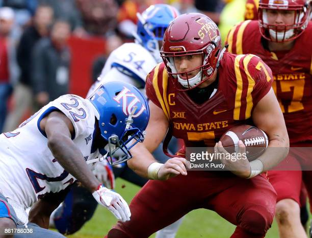 Quarterback Joel Lanning of the Iowa State Cyclones is tackled by safety Tyrone Miller Jr #22 of the Kansas Jayhawks as he scrambles for yards in the...