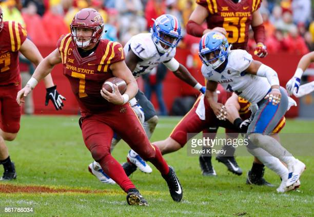 Quarterback Joel Lanning of the Iowa State Cyclones scrambles for yards past safety Mike Lee and safety Bryce Torneden of the Kansas Jayhawks in the...