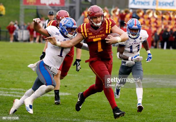 Quarterback Joel Lanning of the Iowa State Cyclones scrambles is tackled by safety Mike Lee and safety Bryce Torneden of the Kansas Jayhawks in the...
