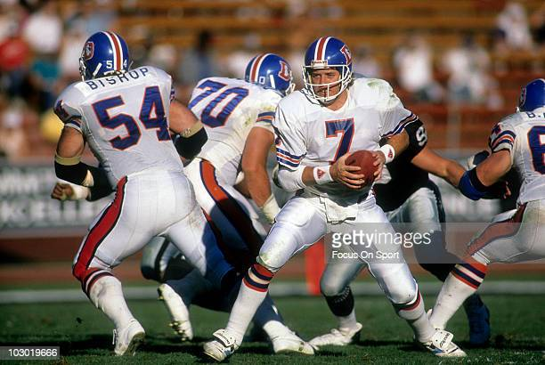 Quarterback John Elway of the Denver Broncos from under center turns and drops back to pass against the Los Angeles Raiders December 4 1988 during an...