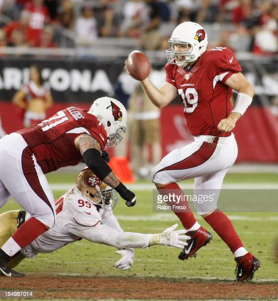 Quarterback John Skelton of the Arizona Cardinals avoids a sack by Aldon Smith of the San Francisco 49ers as he dives past the block of Daryn...