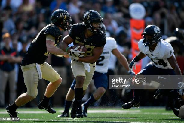 Quarterback John Wolford hands the football off to running back Matt Colburn of the Wake Forest Demon Deacons during the Deacons' football game...