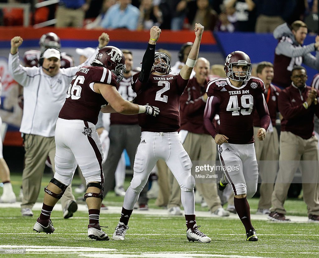 Quarterback <a gi-track='captionPersonalityLinkClicked' href=/galleries/search?phrase=Johnny+Manziel&family=editorial&specificpeople=9703372 ng-click='$event.stopPropagation()'>Johnny Manziel</a> #2 of the Texas A&M Aggies celebrates with teammates Mike Matthews #56 and Josh Lambo #49 after a touchdown during the Chick-fil-A Bowl game against the Duke Blue Devils at the Georgia Dome on December 31, 2013 in Atlanta, Georgia.