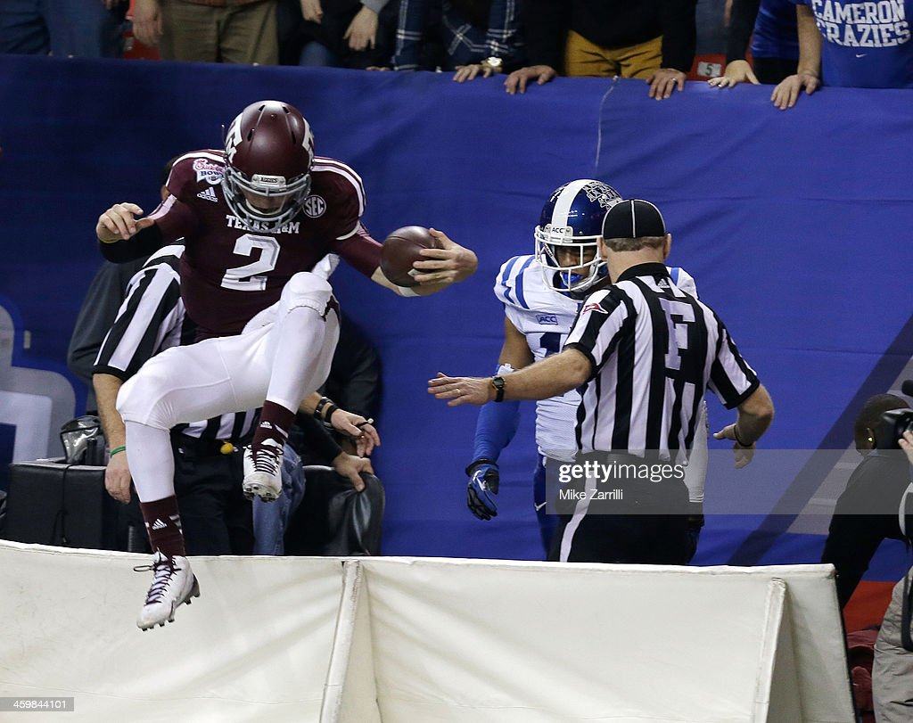 Quarterback <a gi-track='captionPersonalityLinkClicked' href=/galleries/search?phrase=Johnny+Manziel&family=editorial&specificpeople=9703372 ng-click='$event.stopPropagation()'>Johnny Manziel</a> #2 of the Texas A&M Aggies jumps over the field signage back onto the field after scoring a touchdown during the Chick-fil-A Bowl game against the Duke Blue Devils at the Georgia Dome on December 31, 2013 in Atlanta, Georgia.