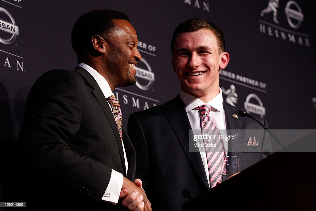 Quarterback Johnny Manziel (R) of the Texas A&M University Aggies and head coach Kevin Sumlin (L) pose after being named the 78th Heisman Memorial Trophy Award winner at a press conference at the Marriott Marquis on December 8, 2012 in New York City.