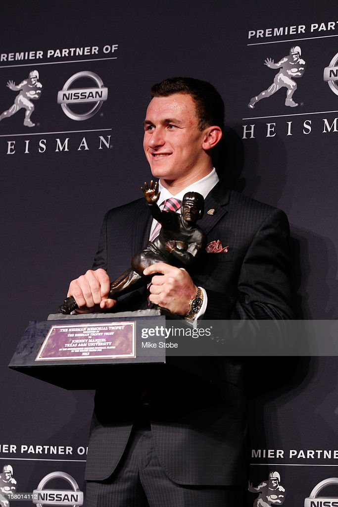 Quarterback Johnny Manziel of the Texas A&M University Aggies poses with the Heisman Memorial Trophy after being named the 78th Heisman Memorial Trophy Award winner at a press conference after at the Marriott Marquis on December 8, 2012 in New York City.