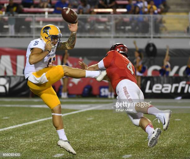 Quarterback Johnny Stanton of the UNLV Rebels blocks a punt by punter Michael Carrizosa of the San Jose State Spartans during their game at Sam Boyd...