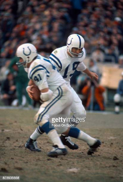 Quarterback Johnny Unitas of the Baltimore Colts hands off to running back Tom Matte against the New York Jets during an NFL football game November...
