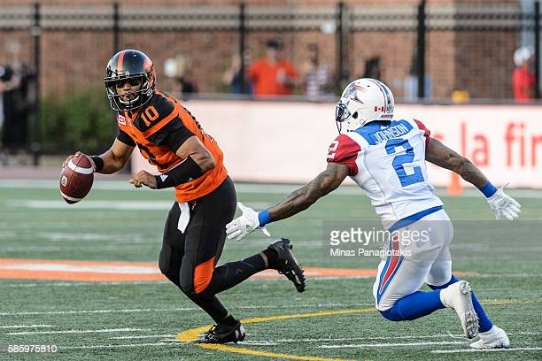Quarterback Jonathon Jennings of the BC Lions looks to play the ball past cornerback Jovon Johnson of the Montreal Alouettes during the CFL game at...