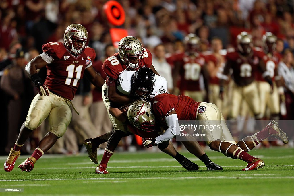 Quarterback Jordan Lynch of the Northern Illinois Huskies is tackled by Lamarcus Joyner #20 and Tyler Hunter #1 of the Florida State Seminoles during the Discover Orange Bowl at Sun Life Stadium on January 1, 2013 in Miami Gardens, Florida.