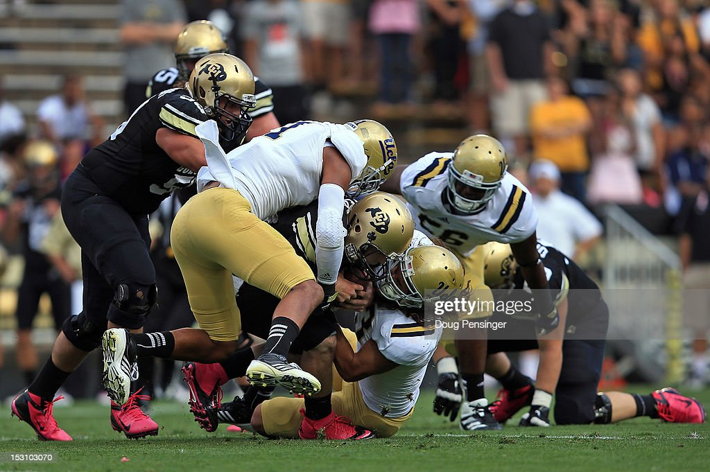 Quarterback Jordan Webb #4 of the Colorado Buffaloes is sacked by linebacker Anthony Barr #11 of the UCLA Bruins and linebacker Damien Holmes #43 of the UCLA Bruins at Folsom Field on September 29, 2012 in Boulder, Colorado. UCLA defeated Colorado 42-14.